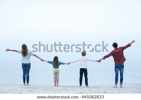 Rear view of family holding hands while standing at sea shore against sky