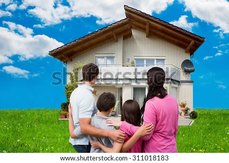 Rear view of family looking at new house on grassy field against sky