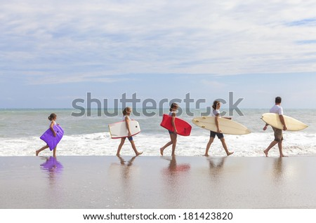 Rear view of family mother, father, daughter, parents and female girl children going surfing with surfborards on a sunny vacation day  - stock photo