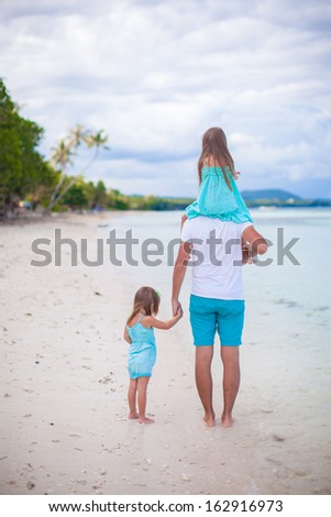 Rear view of Family of three on tropical white beach