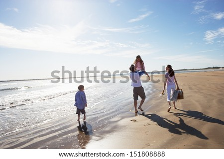 Rear View Of Family Walking Along Beach With Picnic Basket - stock photo
