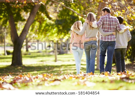Rear View Of Family Walking Through Autumn Woodland - stock photo