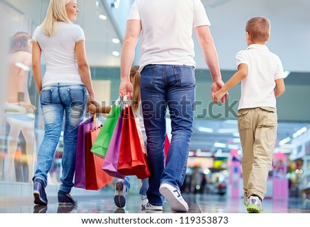 Rear view of family with paperbags walking in the mall