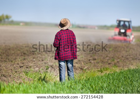 Rear view of farmer with hoe standing on fertile land and looking at tractor plowing soil - stock photo