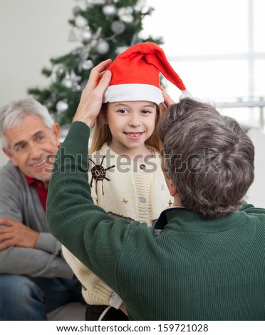 Rear view of father adjusting girl's Santa hat with grandfather looking at them in house - stock photo