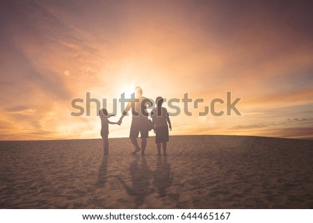 Rear view of father and children pointing and looking something while walking on desert