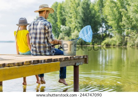 Rear view of father and daughter sitting on bridge and fishing - stock photo