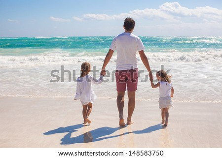 Rear view of father and his two cute daughters walking on white sand beach - stock photo