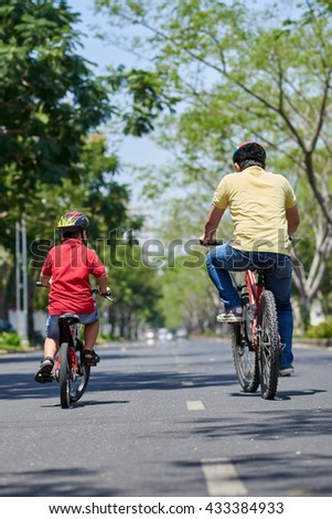 Rear view of father and son enjoying cycling along the road