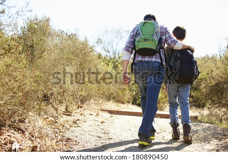 Rear View Of Father And Son Hiking In Countryside - stock photo