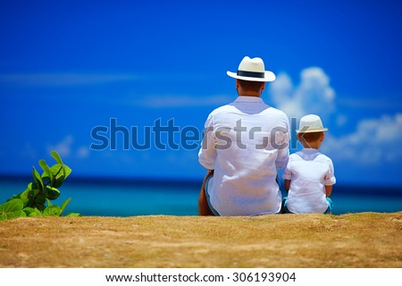 rear view of father and son sitting together on sky horizon - stock photo