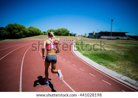 Rear view of female athlete running on the racing track on a sunny day - stock photo