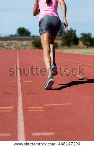 Rear view of female athlete running on the running track on a sunny day - stock photo