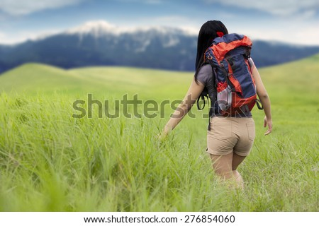 Rear view of female backpacker walking on the meadow while carrying backpack for hiking - stock photo