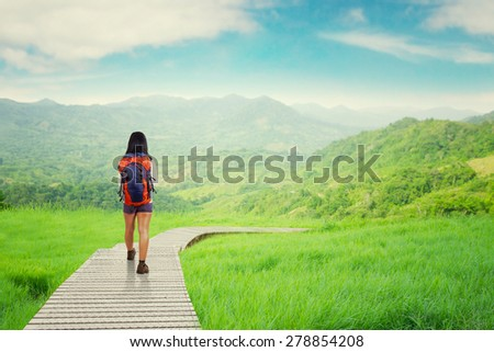 Rear view of female backpacker walking on the wood path while carrying backpack for hiking - stock photo