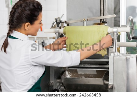 Rear view of female chef processing ravioli pasta in machinery at commercial kitchen