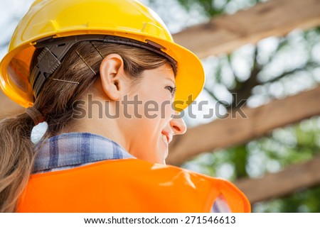 Rear view of female construction worker looking away at site