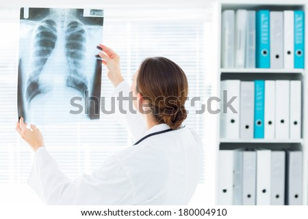 Rear view of female doctor studying Xray report in clinic - stock photo