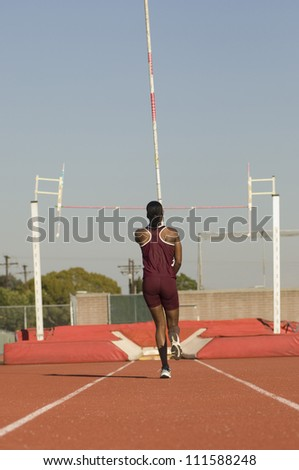Rear view of female pole vaulter running with pole