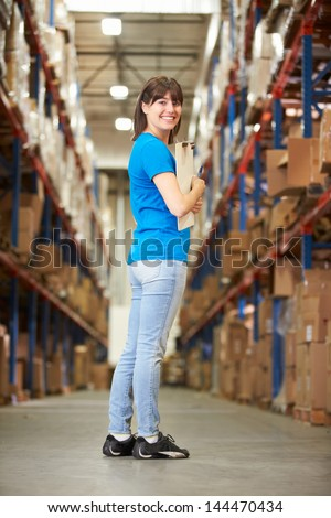 Rear View Of Female Worker In Distribution Warehouse - stock photo