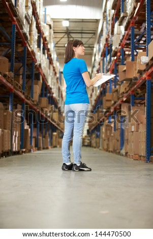 Rear View Of Female Worker In Distribution Warehouse