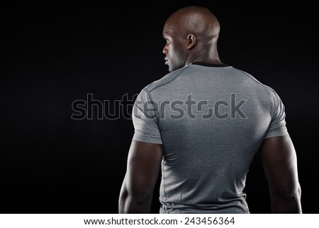 Rear view of fit young man with muscular build standing against black background. Afro american fitness model looking at copy space. - stock photo