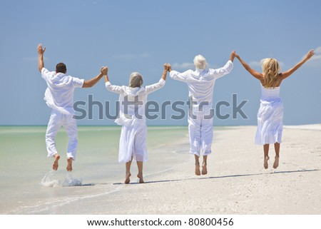 Rear view of four people, two seniors, couples or family generations, holding hands, having fun and jumping in celebration on a tropical beach - stock photo
