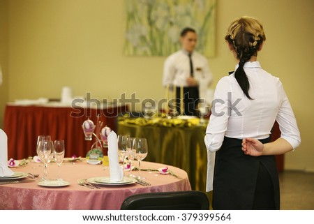 Rear view of girl. waiter ready to service - stock photo