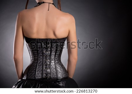 Rear view of gothic girl in silver leather corset with stars pattern, copy-space for your text   - stock photo