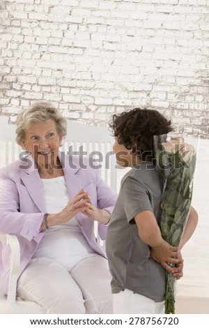 Rear view of grand sun holding flowers  behind back with his grandmother looking at him surprised - stock photo