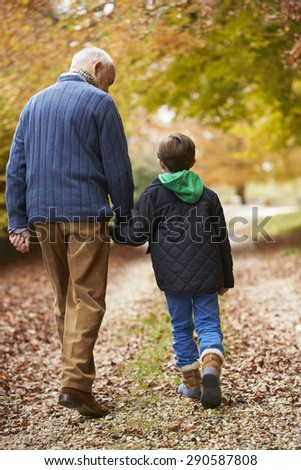 Rear View Of Grandfather And Grandson Walking Along Path - stock photo