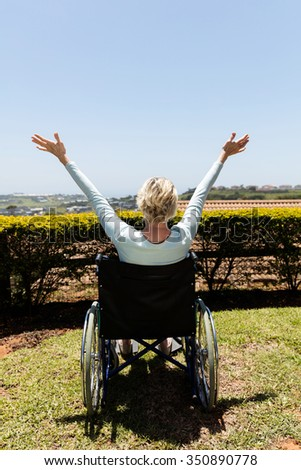 rear view of handicapped senior woman with open arms in home garden - stock photo
