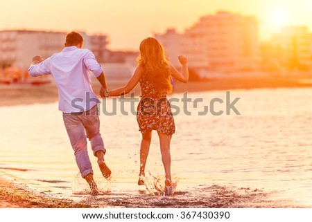 Rear view of happy couple running in summer on the beach in a tropical place. Two lovers in vacation in an idyllic nature scene sharing positive feelings and emotions. Magic moments  of loving hearts. - stock photo