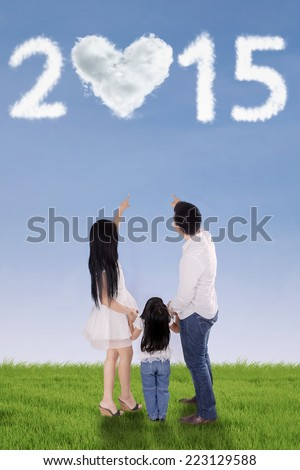 Rear view of happy family standing on meadow while pointing at cloud shaped number 2015