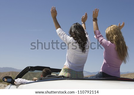 Rear view of happy friends enjoying their journey in car - stock photo