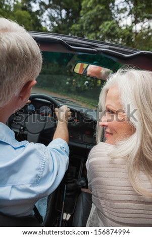 Rear view of happy mature couple going for a ride together in classy convertible - stock photo