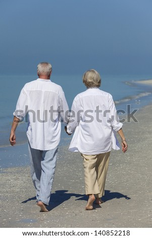 Rear view of happy senior man and woman couple walking and holding hands on a deserted tropical beach with bright clear blue sky - stock photo