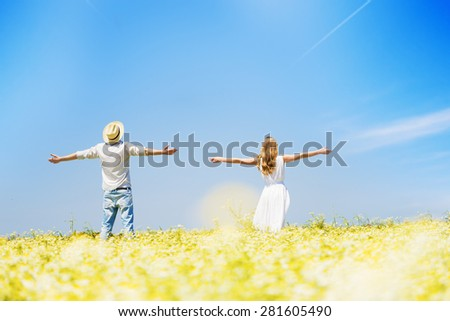 Rear view of happy, young couple with arms outstretched in chamomile , daisy field.Unrecognizable people - stock photo