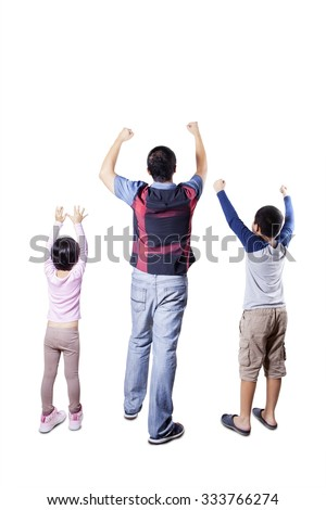Rear view of happy young father and his children standing in the studio and raise hands together