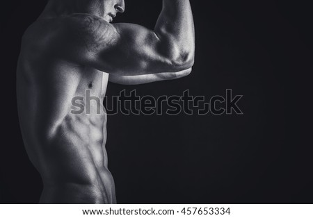 Rear view of healthy muscular young man isolated on black background. Studio shot. Copy-space.