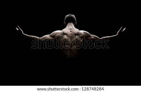Rear view of healthy muscular young man with his arms stretched out isolated on black background - stock photo