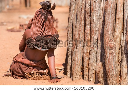 Rear view of himba woman outside shack - stock photo