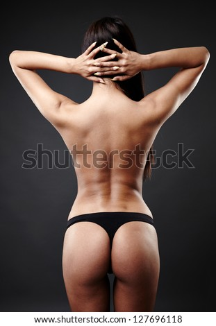 Rear view of hot Arab woman dancing over gray background - stock photo