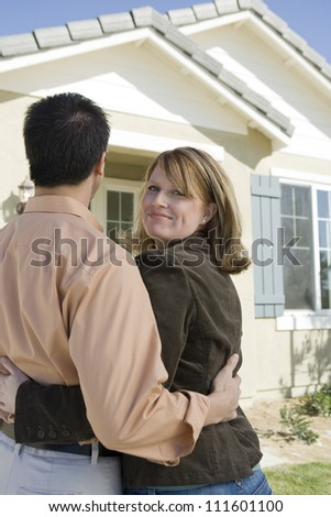 Rear view of interracial couple standing in front of a new home
