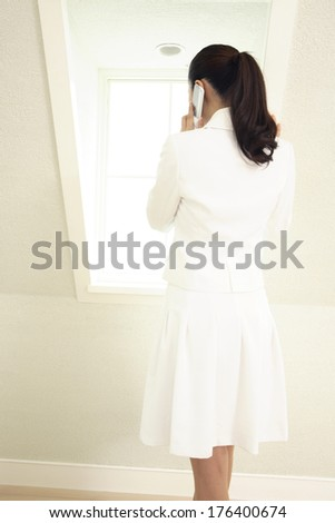 Rear View of Japanese businesswoman talking on mobile phone