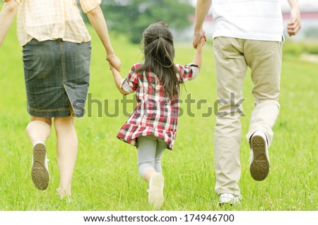 Rear View of Japanese girl walking hand in hand with parents - stock photo