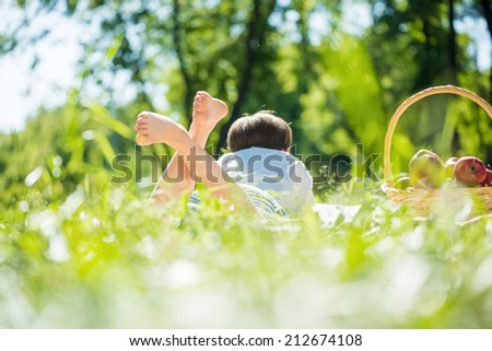 Rear view of kid laying on blanket in park