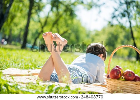 Rear view of kid laying on blanket in park - stock photo