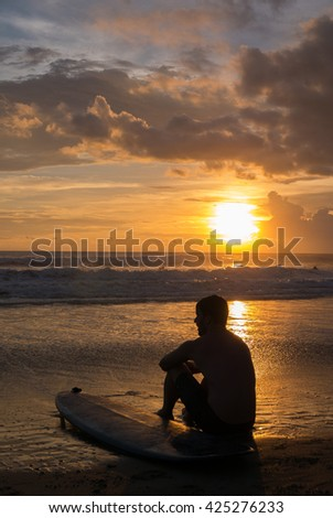Rear view of lean young shirtless Caucasian man sitting on the sand  with his surfing board while watching waves roll in on beautiful beach under the sunset in Chenggu beach, Bali Island. 2016