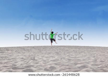 Rear view of little boy enjoy holiday and freedom by jumping on the sand desert under blue sky - stock photo